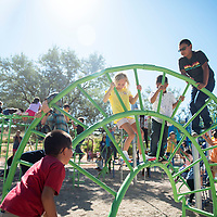 Rehoboth Christian School elementary students play on a flip-flop climber following the dedication of their new playground Tuesday morning. The playground was paid for by fundraising through the color runs and donations.