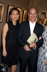Left to right, City figure LUQMAN ARNOLD and his wife CHUMSRI at a private view of fashion designer Lindka Cierach's Couture Dresses drawn by Trudy Good held at the Belgravia Gallery, 45 Albemarle Street, London on 21st September 2005.<br />
