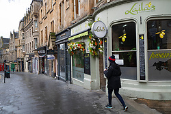 Edinburgh, Scotland, UK. 28 December 2020. Scenes from Edinburgh City Centre as Scotland starts first weekday under the most severe level 4 lockdown with all non-essential businesses closed. Pic; Cockburn Street in the Old Town is almost deserted with shops and cafes closed.  Iain Masterton/Alamy Live News