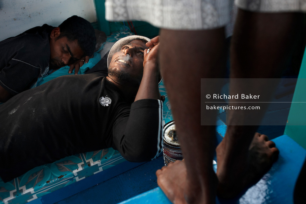 A Maldivian crew rest before a day's yellow fin tuna fishing aboard a traditional dhoni fishing boat on the Indian Ocean