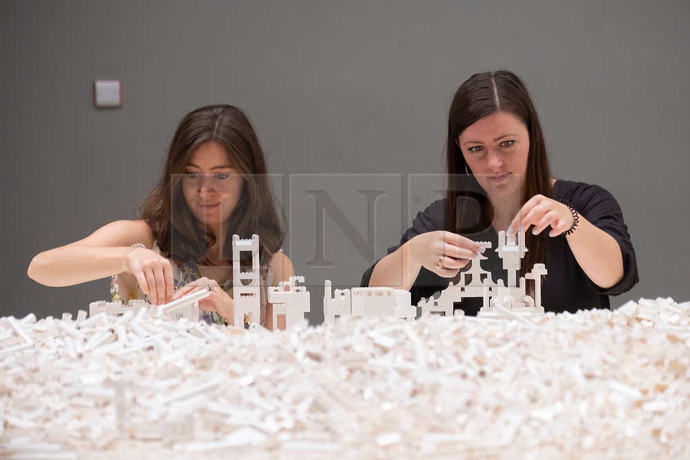 © Licensed to London News Pictures. 26/07/2019. London, UK. Visitors build structures from one tonne of white Lego bricks as part of Olafur Eliasson's The Cubic Structural Evolution Project 2004 installation showing at the Tate Modern. Photo credit: Ray Tang/LNP
