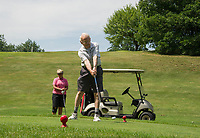 Dale Nims watches as her dad Phillip Roy hits off the first tee at Lochmere Golf & Country Club on Monday morning.  (Karen Bobotas/for the Laconia Daily Sun)