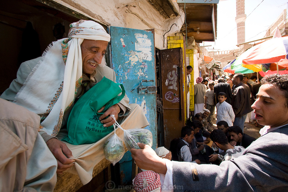 Ahmed Ahmed Swaid, a qat merchant, sits at a market in the old city of Sanaa, Yemen, and sells qat leaves in plastic bags.  (Ahmed Ahmed Swaid is featured in the book What I Eat: Around the World in 80 Diets.) Ahmed, who wears a jambiya dagger as many Yemeni men do, has been a qat dealer in the old city souk for eight years. Although qat chewing isn't as severe a health hazard as smoking tobacco, it has drastic social, economic, and environmental consequences. When chewed, the leaves release a mild stimulant related to amphetamines. Qat is chewed several times a week by a large percentage of the population: 90 percent of Yemen's men and 25 percent of its women. Because growing qat is 10 to 20 times more profitable than other crops, scarce groundwater is being depleted to irrigate it, to the detriment of food crops and agricultural exports.  MODEL RELEASED.
