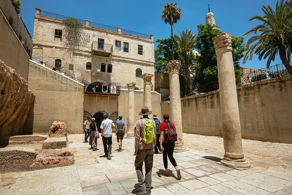 A minaret of a mosque is seen in the background as tourists walk through the Cardo, a north-south oriented main street constructed in the Roman period, in the Jewish Quarter of the Old City of Jerusalem