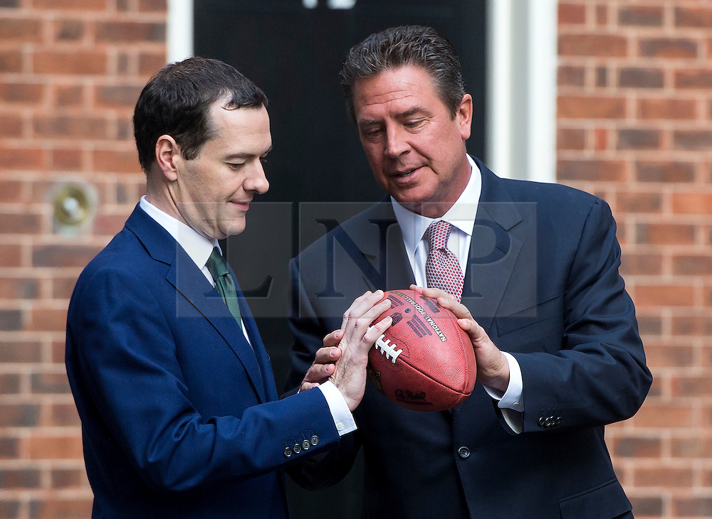 © Licensed to London News Pictures. 02/10/2015. London, UK. British chancellor GEORGE OSBORNE being shown how to throw a football by former Miami Dolphins quarterback DAN MARNO after meeting with NFL team owners, execs and former stars at Downing Street ahead of this weekend NFL game at Wembley stadium.  Photo credit: Ben Cawthra/LNP