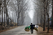 A man carries produces on his back down a road near Dongdaxu Village, Chuzhou, Anhui Province, China on 02 March, 2011.  Dongdaxu Village is  the ancestral home of current Chinese vice premier Li Keqiang, slated to be the next premier and the man in charge of China's economic transformation