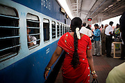 Jasmine flowers in the hair of South Indian women as they walk the length of the Himsagar Express 6318 to look for their coach as it stops for 20 minutes at Erode Junction stn., Tamil Nadu on 9th July 2009.. .6318 / Himsagar Express, India's longest single train journey, spanning 3720 kms, going from the mountains (Hima) to the seas (Sagar), from Jammu and Kashmir state of the Indian Himalayas to Kanyakumari, which is the southern most tip of India...Photo by Suzanne Lee / for The National