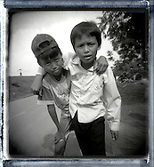 Portrait of two kids standing close from a road