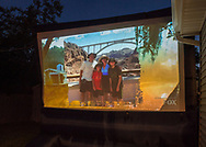 """Merrick, New York, USA. 11th June 2017.  Family vacation photo shown on large screen is of """"American Grit"""" TV show contestant CHRIS EDOM, now 48 of Merrick, during Season 2 premiere of the reality show. Edom family's relatives and neighbors watched Episode 1 of the Fox network TV show on large screen in their backyard."""
