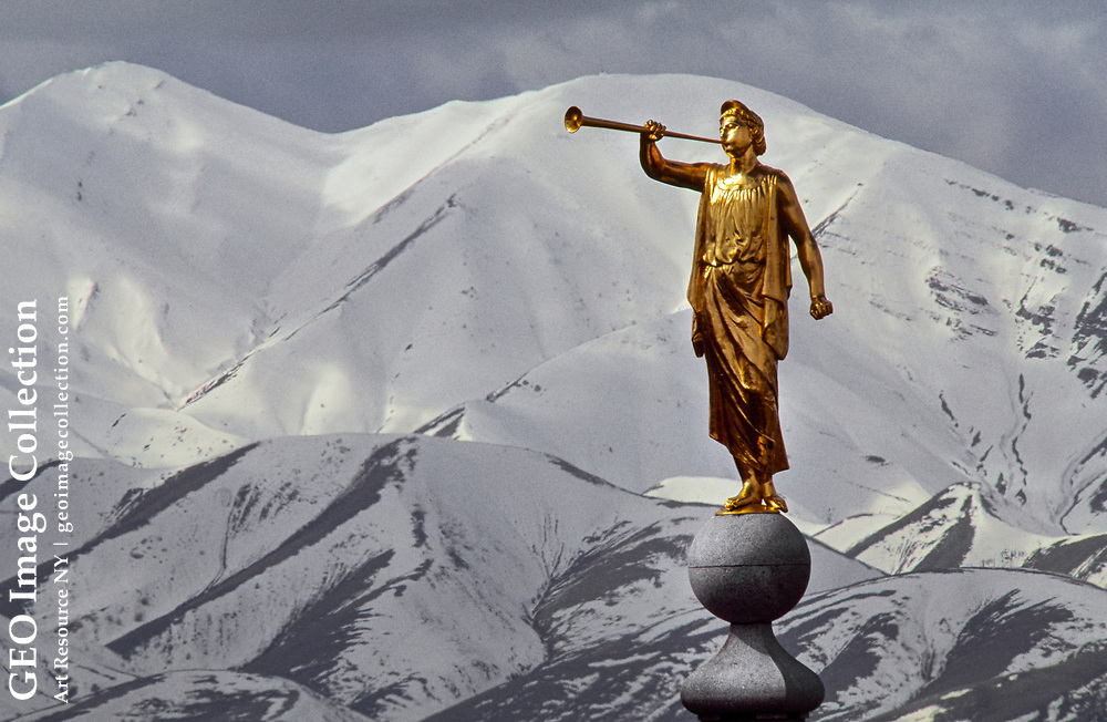The gilded statue of the Angel Moroni against the Oquirrh Mountains.