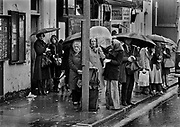 Queue waiting for bus in North Kensington in rain. Coming and Going is a project commissioned by the Museum of London for photographer Barry Lewis in 1976 to document the transport system as it is used by passengers and commuters using public transport by trains, tubes and buses in London, UK.