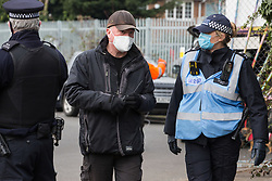 Sipson, UK. 8th March, 2021. Karl Harrison (c) of the National Eviction Team (NET) speaks to a Metropolitan Police liaison officer during an operation to evict residents from the remaining section of a squatted off-grid eco-community garden known as Grow Heathrow. Grow Heathrow was founded in 2010 on a previously derelict site close to Heathrow airport in protest against government plans for a third runway and has since made a significant educational and spiritual contribution to life in the Heathrow villages which are threatened by airport expansion.