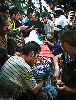 Ramallah, West Bank --  The body of slain Palestinian and Fatah member Riad Hamoudi, 30, a iron worker and father of two children is kissed by a mourner as he is placed in tomb at the Cemetery of the Al-Bireh in Ramallah, West Bank on Monday, October 16, 2000.  -- Photo by Jack Gruber, USA TODAY