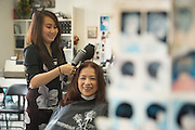 Helen Do gives Tina's Hair Design owner Tina Chang a blow dry at Tina's Hair Design in Milpitas, California, on September 11, 2014. (Stan Olszewski/SOSKIphoto)