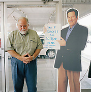 Sandy Stillions, car salesman with his head bowed next to a card board cut of another salesman. From a series of portraits of car salesmen taken in the southern states of America.