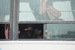 Licensed to London News Pictures. 10/11/2016. Mosul, Iraq. A young Iraqi woman, wearing a niqab looks from a bus window as she and other families, escaping from areas within the city where fighting between Iraqi Security Forces and Islamic State militants is taking place, wait to be evacuated by the Iraqi Army from the city's Gogjali District.<br /> <br /> The battle to retake Mosul, which fell June 2014, started on the 16th of October 2016 with Iraqi Security Forces eventually reaching the city on the 1st of November. Since then elements of the Iraq Army and Police have succeeded in pushing into the city and retaking several neighbourhoods allowing civilians living there to be evacuated - though many more remain trapped within Mosul. Photo credit: Matt Cetti-Roberts/LNP