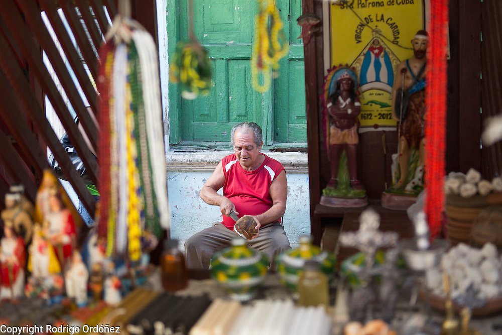 A man uses a knife to open a coconut behind a stall selling items used in Santeria rituals at a traditional market in Santiago de Cuba, Cuba, on December 27, 2014.