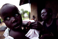 Rose's mother dresses her granddaughter at her house in Nimule.