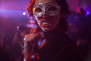 A masked, fanged woman at the ball.