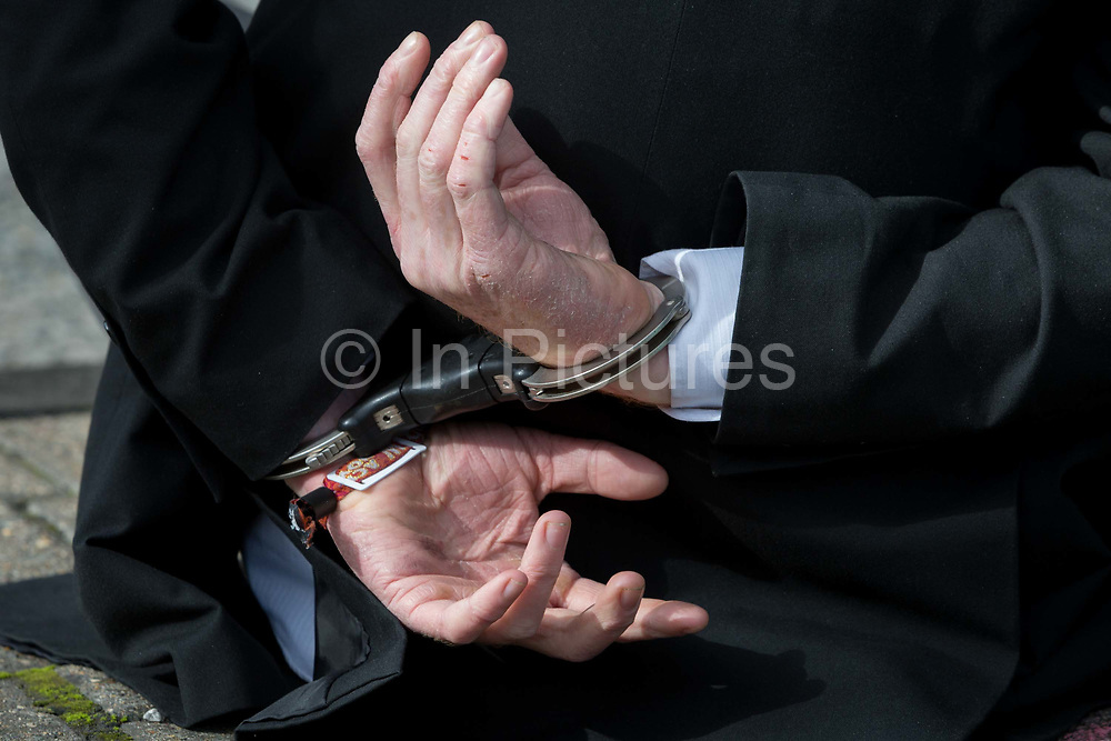 A detail of hands in handcuffs after an environmental activist has been arrested while protesting about Climate Change during the occupation of City Airport Londons Business Travel hub in east London, the fourth day of a two-week prolonged worldwide protest by members of Extinction Rebellion, on 10th October 2019, in London, England.