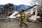 A fire fighter carries a burnt beam as multiple fire departments including Milpitas Fire Department, Spring Valley Fire Department, and Cal Fire, work to contain and extinguish a structure fire at the 3000 block of Calaveras Road near Spring Valley Golf Course in Milpitas, California, on February 10, 2014. (Stan Olszewski/SOSKIphoto)