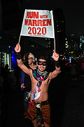 "New York, NY - 31 October 2019. the annual Greenwich Village Halloween Parade along Manhattan's 6th Avenue. A man carries a sign reading ""Run with Warren 2020 NYC Marathon 2019."""