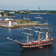 The Oliver Hazard Perry sails past Portsmouth Light House and Fort Constitution at the mouth of  the Piscataqua River off  New Castle, NH during the Parade of Sail event, August, 2016.