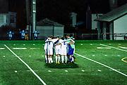 Soccer team huddles before match.