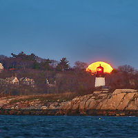 Cold Full moon setting behind Ten Pound Island Lighthouse in Gloucester Massachusetts on Cape Ann.<br />