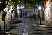 Young men walking on Cuesta de Carvajal cobbled street in Salamanca, Spain