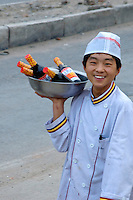 China, Beijing, Chaoyang, San Jian Fang, 2008. Happy to still have a job, a restaurant worker flashes a smile as he transports goods from the shell of the old to the kitchen of the new.