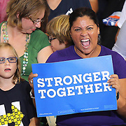 Roxy Santiago of the Human Rights Campaign cheers as Democratic presidential candidate Hillary Clinton speaks during a campaign stop at the Frontline Outreach Center in Orlando, Fla., on Wednesday, Sept. 21, 2016. (Alex Menendez via AP)