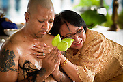 28 JUNE 2011 - CHIANG MAI, THAILAND: A man's mother says goodbye as he is being ordained as a Buddhist monk at Wat Phrathat Doi Saket a large temple complex in Chiang Mai, Thailand. The temple at Doi Saket is said to have been built in the year 1112, but it has been renovated several times since then. Most Thai males enter the Buddhist clergy, called the Sangha, at least once in their lives. Their stay in the monastery can be as short as one week or a lifetime committment, depending on the man. Monks are not allowed to have physical contact with females, including family members, during their time in the monastery.    PHOTO BY JACK KURTZ