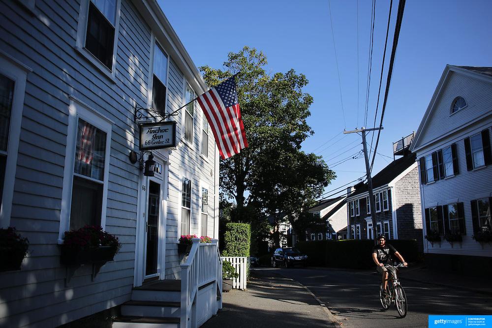 A cyclist in the streets of Nantucket Town Center, Nantucket, Nantucket Island, Massachusetts, USA. Photo Tim Clayton