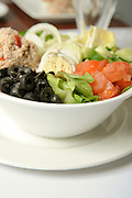 Fresh vegetable salad with black olives and egg