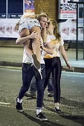 © Licensed to London News Pictures . 17/11/2013 .  Manchester , UK . A man carries a woman across the street . Students from Manchester's Universities take part in the annual Carnage pub crawl event at bars in the city's Deansgate Locks venue . Photo credit : Joel Goodman/LNP
