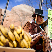 """040915       Cable Hoover<br /> <br /> Activist Nicole Walker carries a sign exclaiming """"No More Monkey Business"""" while handing out bananas outside the Navajo Nation Council Chambers in Window Rock Thursday."""