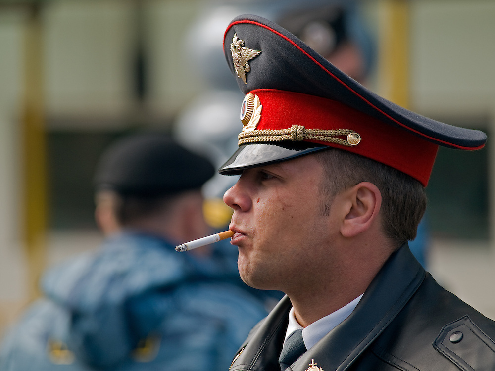 Junger rauchender Polizist (Milizionaer)  an der absperrten Prachtstrasse Twerskaja vor dem Beginn der groessten Militaerparade in Russland seit Ende der Sowjetunion 1991 (9.Mai 2008).<br /> <br /> Young smoking policeman (militiaman) blocking a street in the center of Moscow shortly before the Victory Day parade started (took place the 9th of May 2008) which showcased military hardware for the first time since the Soviet collapse.
