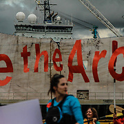 """A sign reads """"save the arctic"""" as 300 kayaktavists paddle out in front of Shell's icebreaker ship to protest arctic oil drilling while in the Port of Portland for repairs. The kayaktavists were able to stall the ship from leaving for 3 days."""