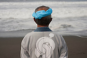 A Mikoshi supporter watches the waves  during the Hamaorisai Matsuri that takes place on Southern Beach in Chigasaki, near Tokyo, Kanagawa, Japan Monday July 18th 2011. The festivals marks the celebration of Marine Day and the rescuing of a divine image that was washed ashore in the area. Over thirty Mikoshi or portable shrines are carried through the night from surrounding shrines to arrive on the beach for sunrise. There they are blessed and then carried into the surf to purify them.