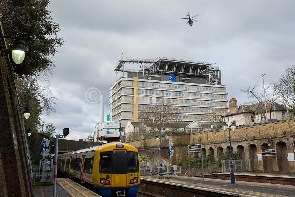 As a helicopter from an Air Ambulance service takes off into overcast skies from the helipad on the roof of Kings College Hospital Trust, a westbound London Overground train leaves nearby Denmark Hill station which is used by many travelling outpatients and visitors to this vital NHS Trust, on 27th February 2020, in London, England.