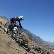 Raphael Kammiein-Cutler from Dunedin in action during the New Zealand South Island Downhill Cup Mountain Bike series held on The Remarkables face with a stunning backdrop of the Wakatipu Basin. 150 riders took part in the two day event. Queenstown, Otago, New Zealand. 9th January 2012. Photo Tim Clayton