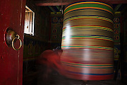 Trekker Ethan Welty spins the giant prayer wheel at the Buddhist nunnery in Devuche along the trail to Everest, Khumbu (Mount Everest) region, Sagarmatha National Park, Himalaya Mountains, Nepal.