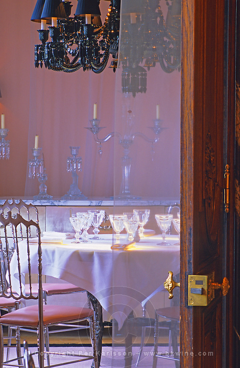 "The private dining room with the black crystal chandelier seen through a door with a brass handle at The Baccarat Restaurant ""Le Cristal Room"", in the old dining room. Crystal chandeliers and glasses. Designed by Philippe Starck. The Cristal Room restaurant: the private dining room with the unique black crystal chandelier"