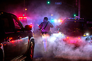 """A California Highway Patrol official runs through flares to get to his car, in search for a gunman near 19th Avenue and Sloat Boulevard on Friday, Oct. 14, 2016 in San Francisco, Calif. The gunman had shot an S.F. police officer in the head and fled. The suspect later emerged from bushes near 28th Avenue and Vicente Street. Still armed, the suspect was shot during a confrontation and apprehended after police deployed flash-bang stun grenades to distract him. The suspect later died from his injuries. The wounded police officer, Kevin Downs, survived and underwent surgery to remove bullet fragments from his brain. Downs and officers had been responding to reports of a man acting erratically and making threats. The suspect's family said Nicholas McWherter was struggling with mental illness and """"lost his way."""""""