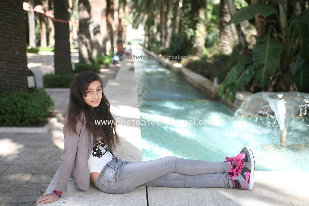 Young girl of 12 relaxing outdoors Photographed at Gan Hamoshava, Rishon Lezion, Israel