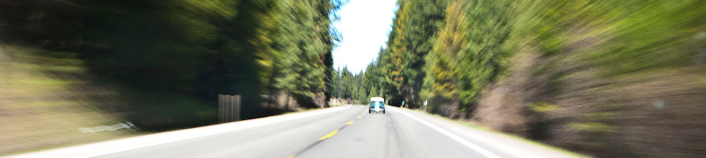 scene along a cross country trip with in a classic Mini Cooper auto - whizzing through the Oregon Cascade Range in a classic Mini Cooper automobile motion blur panorama