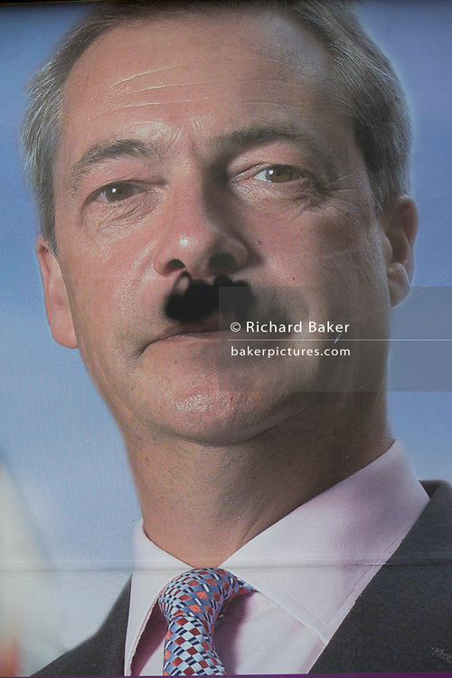 An anti-EU membership 'UK Independence Party's (UKIP) political billboard showing party leader Nigel Farage with a daubed Hitler moustache in East Dulwich - a relatively affluent district of south London. The ad is displayed before European elections on 22nd May.