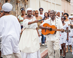 Jahweh David , left, with Glenn Kwabena Davis lead the procession with a selection of Bamboula songs from the period.  10th Annual Dollar Fo' Dollar Culture & History Tour commemorating the anniversary of the successful protest  demanding better pay by Queen Coziah and the 19th century coal laborers in the streets of downtown Charlotte Amalie.  12 September 2015.  St. Thomas, VI.  © Aisha-Zakiya Boyd