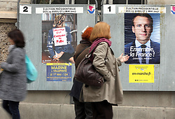 May 6, 2017 - Paris, FRANCE - Residents walk past elections posters displaying centrist presidential contender, Emmanuel Macron (R) and nationalist Marine Le Pen on the eve of the runoff for France's top job May 6, 2017.  Macron is leading in the polls against Le Pen with some 60% vote intentions in an election were voters have unexpectedly spurned mainstream political leaders for mavericks. (Credit Image: © Maya Vidon-White via ZUMA Wire)